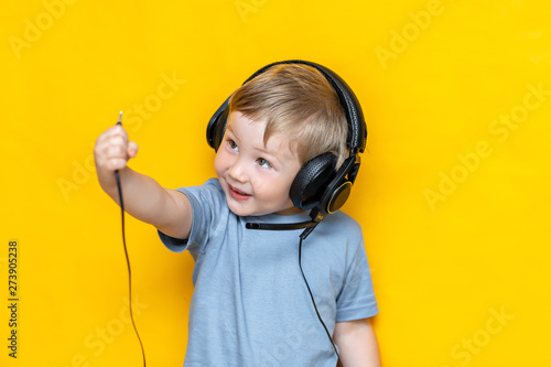 A smiling boy unplug his headphone and show plug to camera on isolated yellow background - 273905238