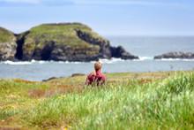 Girl Walking In Field Near Atlantic Ocean In Newfoundland