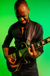 canvas print picture - Young african-american musician playing the guitar like a rockstar on gradient green-yellow background. Concept of music, hobby, festival, open-air. Joyful attractive guy improvising, singing song.