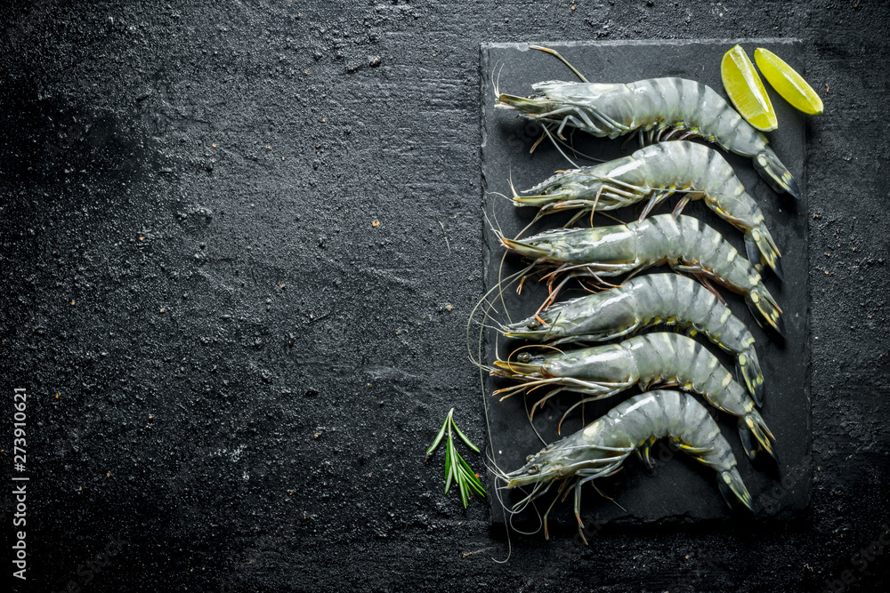 Fototapety, obrazy: Fresh raw shrimps on a stone Board with lime slices.
