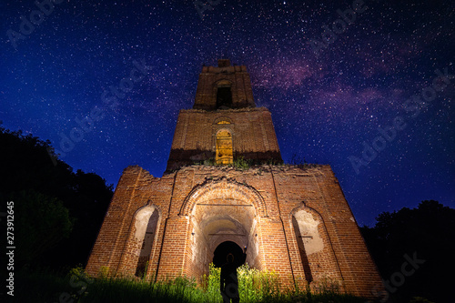 night bell tower ruin in forest at starry night and man with flashlight under it