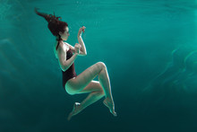 Deep Dive, Concept. A Slender Young Woman Is Swimming Underwater.