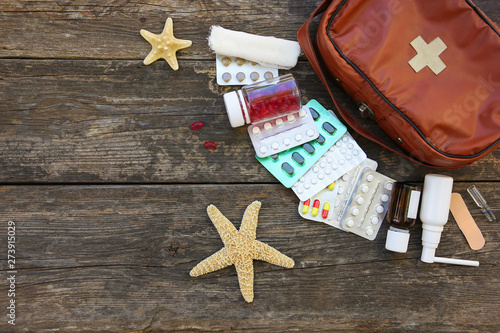Fotografia  First aid kit on old wooden background