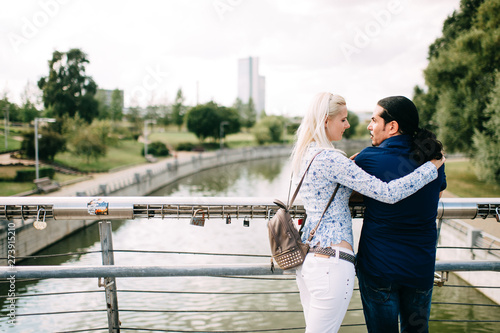Stampa su Tela rear view of Young couple in love are hugging on bridge