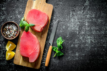 Fresh Raw Tuna Steak On A Wooden Cutting Board With Lemon Slices, Spices And Mint.