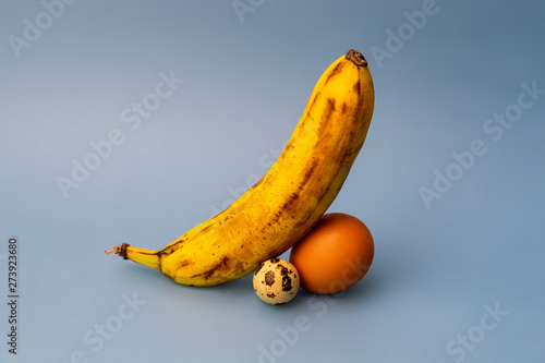 two eggs of different sizes and banana composing a penis Tablou Canvas