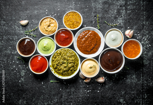 Pesto sauce, guacomole, ketchup, mustard, barbecue sauce in bowls Wallpaper Mural