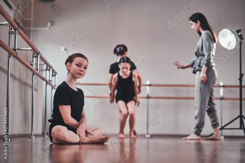 Fototapety, obrazy: Little pretty ballerina is sitting on the floor while her other classmates doing exercises with trainer.