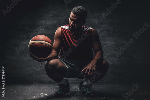 Fotografiet  Full body portrait of a black basketball player sits on a floor and holds basket ball