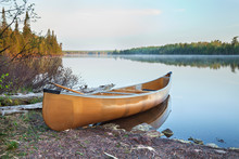 Yellow Canoe On Shore Of Northern Minnesota Lake In Early Morning Light