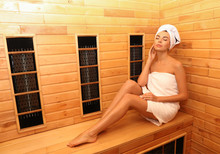 Young Woman Sitting On Wooden Bench In Infrared Sauna, Space For Text. Spa Treatment