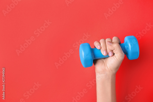Fotografia  Woman holding vinyl dumbbell on color background, closeup with space for text