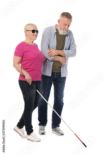 Mature man helping blind person with long cane on white background