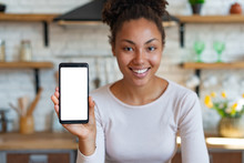 Young Smiling Mulatto Woman Sits And Showing A Mockup With White Screen Of Cell Telephone . - Image
