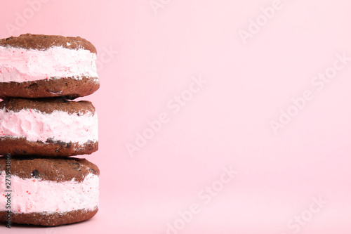 Sweet delicious ice cream cookie sandwiches on color background, space for text