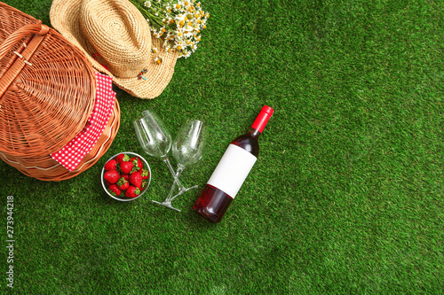 Poster Londres Flat lay composition with picnic basket, wine and strawberries on grass, space for text