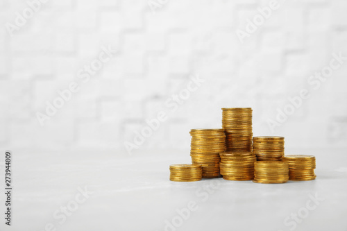 Valokuvatapetti Many stacks of coins on table against light background, space for text