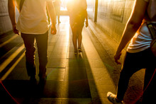 Silhouettes Of People Walking In A Dark Tunnel Against A White Glow