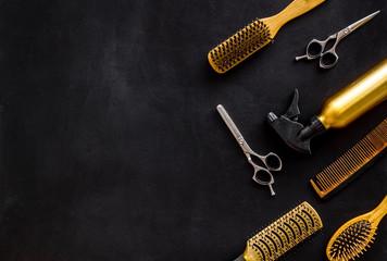 Češljevi i frizerski alati u radnom stolu salona za uljepšavanje na crnoj pozadini pogleda odozgo