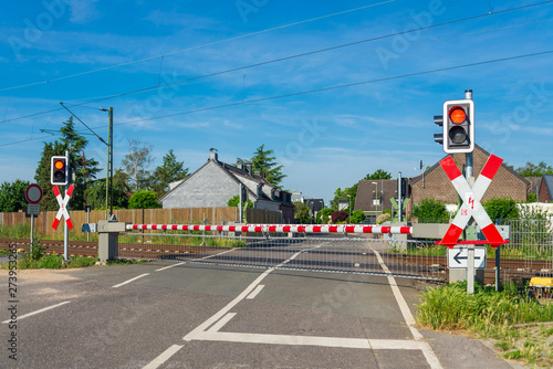 Valokuva  Outdoor sunny street view of level crossing railway barrier and red traffic light at intersection between road and railway in small village Meerbusch, countryside of Düsseldorf, Germany