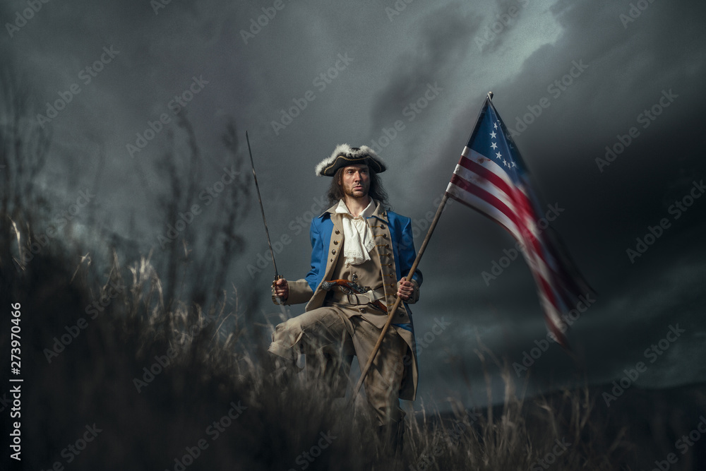 Fototapety, obrazy: American revolution war soldier with flag of colonies and saber over dramatic landscape. 4 july independence day of USA concept photo composition: soldier and flag.