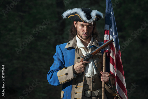 Man dressed as soldier of War of Independence United States aims from pistol with flag Fototapet