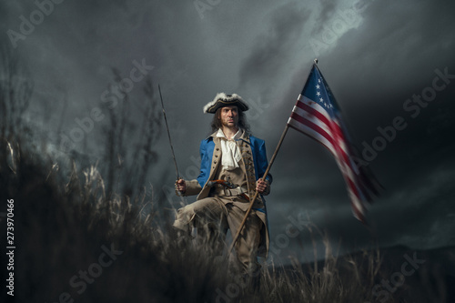 Fotografering American revolution war soldier with flag of colonies and saber over dramatic landscape