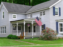 Traditional Style Clapboard House With Large Porch And American Flag