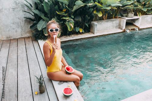 Obraz Girl eating watermelon in pool on luxury villa in Bali - fototapety do salonu