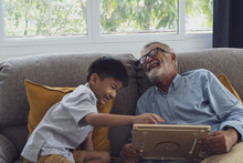 Senior Man Happiness And Grandson Are Sitting On The Sofa And Playing Games And Reading Book At Living Room Together
