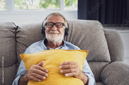 Foto  senior man happiness sitting on the sofa and listening music with headphone at l