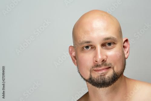 Fototapeta Attractive smiling bald man on gray background in studio