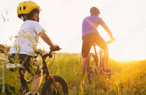 Photo  Father and son together are riding bicycles through the pathway in the field