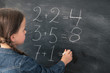 Primary school education. Back view of young girl doing sum on chalkboard at mathematics class.