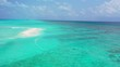 Flying towards a sandbank in turquoise water in the Caribbean Sea. Dolly in, wide angle.