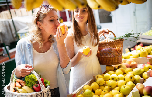 Young women friends baying vegetables and fruits on the market Canvas-taulu