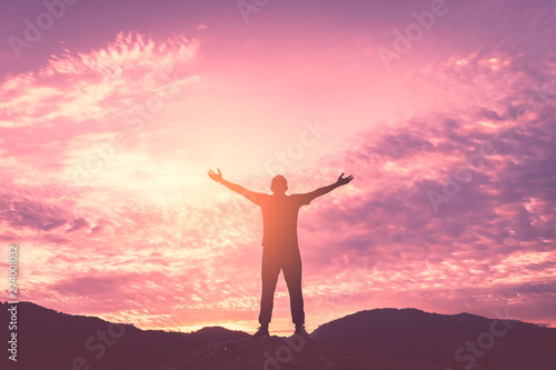 Foto auf AluDibond Rosa hell Backpacker man raise hand up on top of mountain with sunset sky and clouds abstract background.