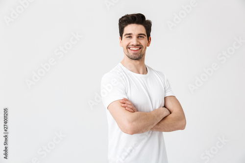 Stampa su Tela  Happy young excited emotional man posing isolated over white wall background