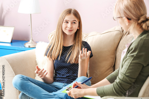 Obraz Female psychologist working with teenage girl in office - fototapety do salonu