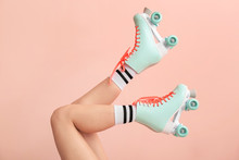Legs Of Woman In Vintage Roller Skates On Color Background