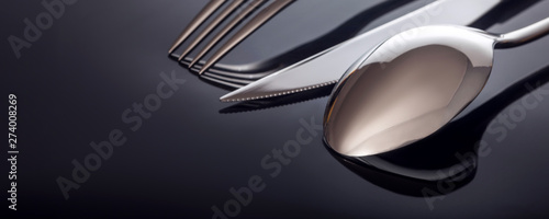 Fototapeta Knife and fork, spoon, on a black background obraz