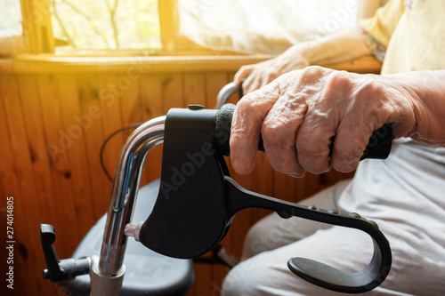 Aging woman holds her wrinkled hand on an adult medical walker sitting on the balcony in bright sunshine Fototapeta