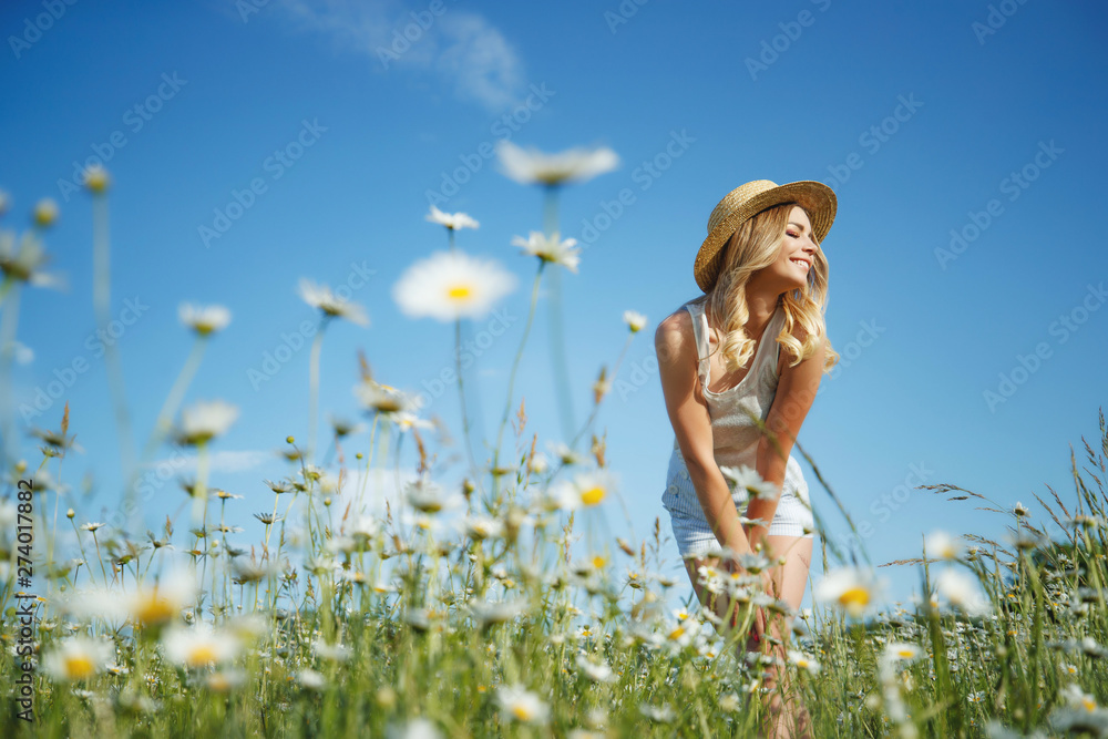 Fototapeta Beautiful woman in the field with flowers.