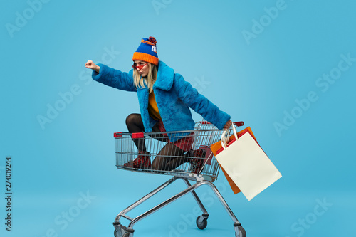 Cuadros en Lienzo Young woman with shopping bags riding trolley