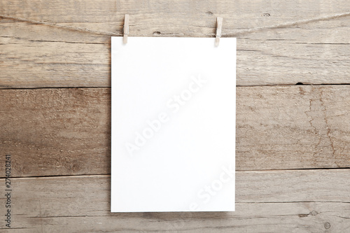 Fotografia  A4 mock up - empty sheet of paper on a wooden background - blank A4 sheet on clo