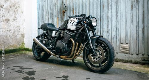 Shiny customized motorcycle parked in front of garage door Fotobehang