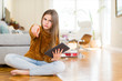 Beautiful young girl kid using digital touchpad tablet sitting on the floor pointing with finger to the camera and to you, hand sign, positive and confident gesture from the front