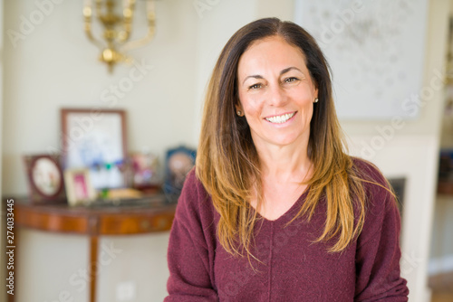 Stampa su Tela  Beautiful middle age woman smiling at home