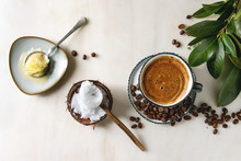 Bulletproof Coffee. Keto Diet Coffee In Blue Ceramic Cup With Organic Ghee Butter And Coconut Cold Press Oil In Spoons With Beans And Green Branch Over White Marble Background. Flat Lay, Space