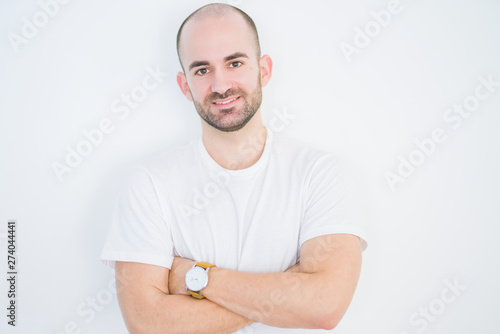 Fototapeta Young bald man over white isolated background happy face smiling with crossed arms looking at the camera